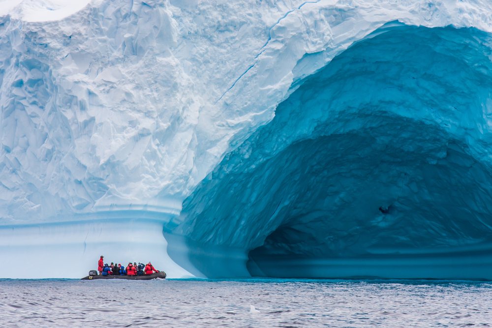 zodiac in front of an very big ice berg
