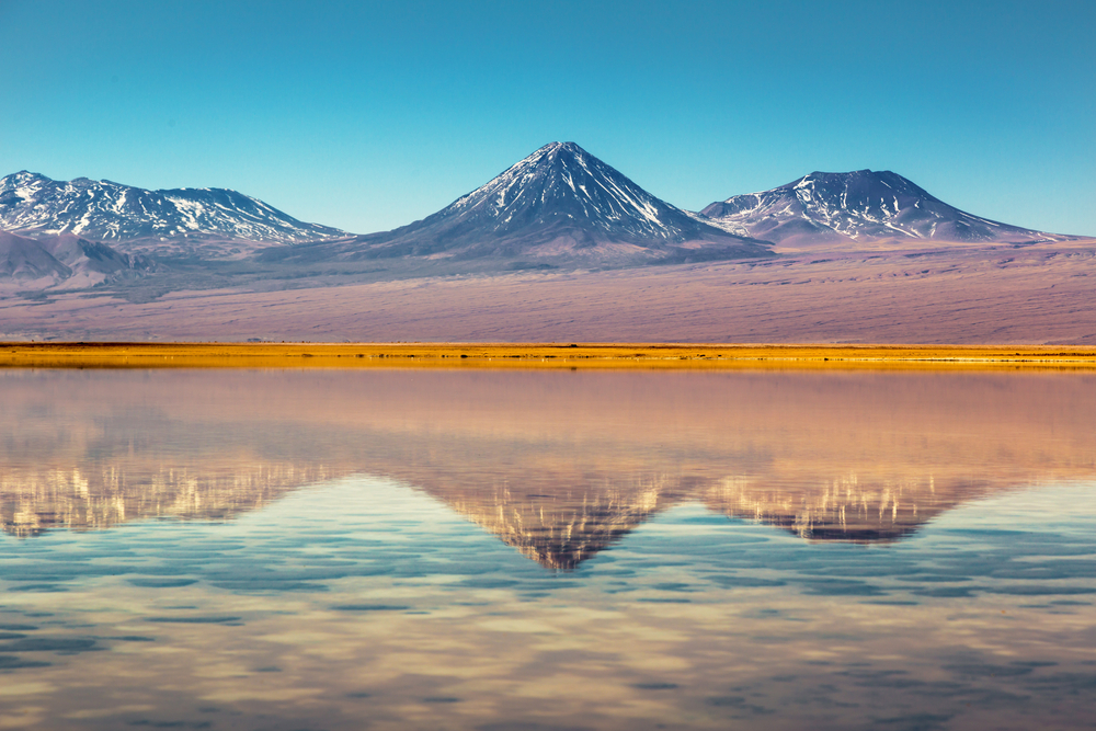mountains with yellow in front and reflection in water atacama chile