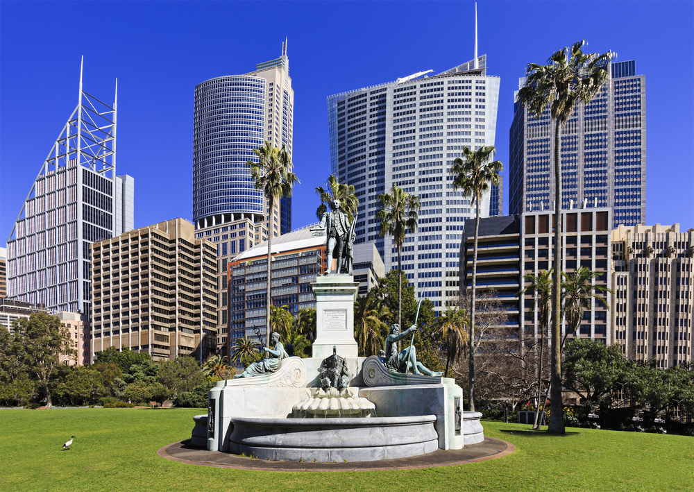 Monument of Captain Arthur Philip - first governor of NSW colony of Sydney, Australia in Royal Botanic Garden against modern city skyscraper towers