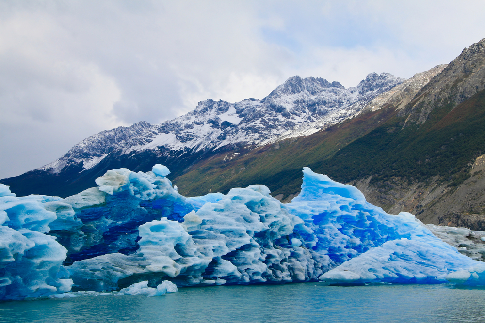 glacier ending in lake with snow capped mountains in the background patagonia