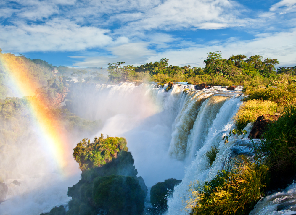 big waterfall with forest around and a rainbow