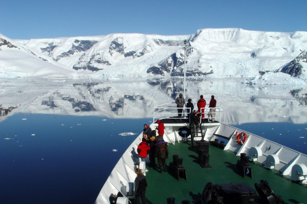 deck of cruise in antarctica with people and snow capped mountains in the background