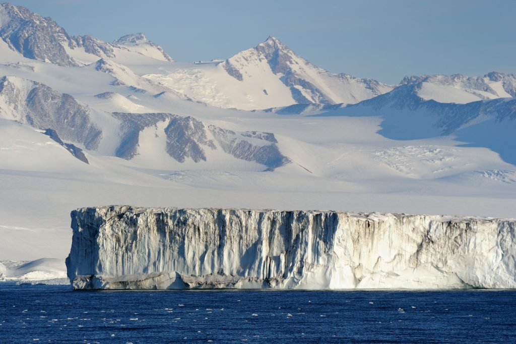 Ice shelf floating on the sea with snow capped mountains in the background in antarctica