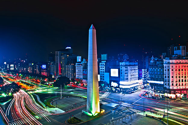 Night time scene of the Obelisk in the centre of Buenos Aires with lights moving around the streets