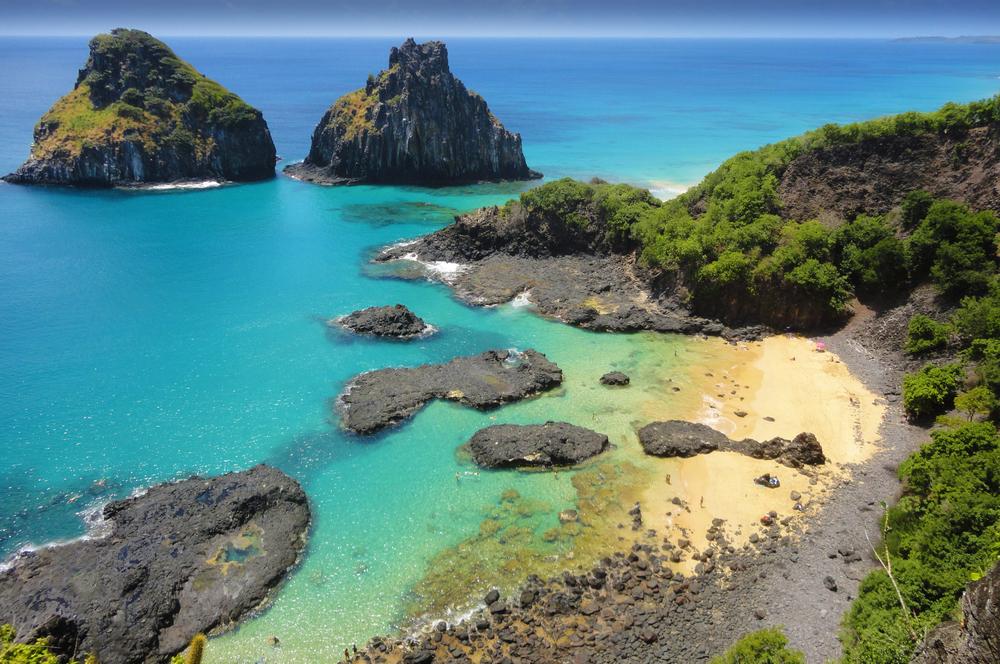 rocky beach in brazil with rock island background