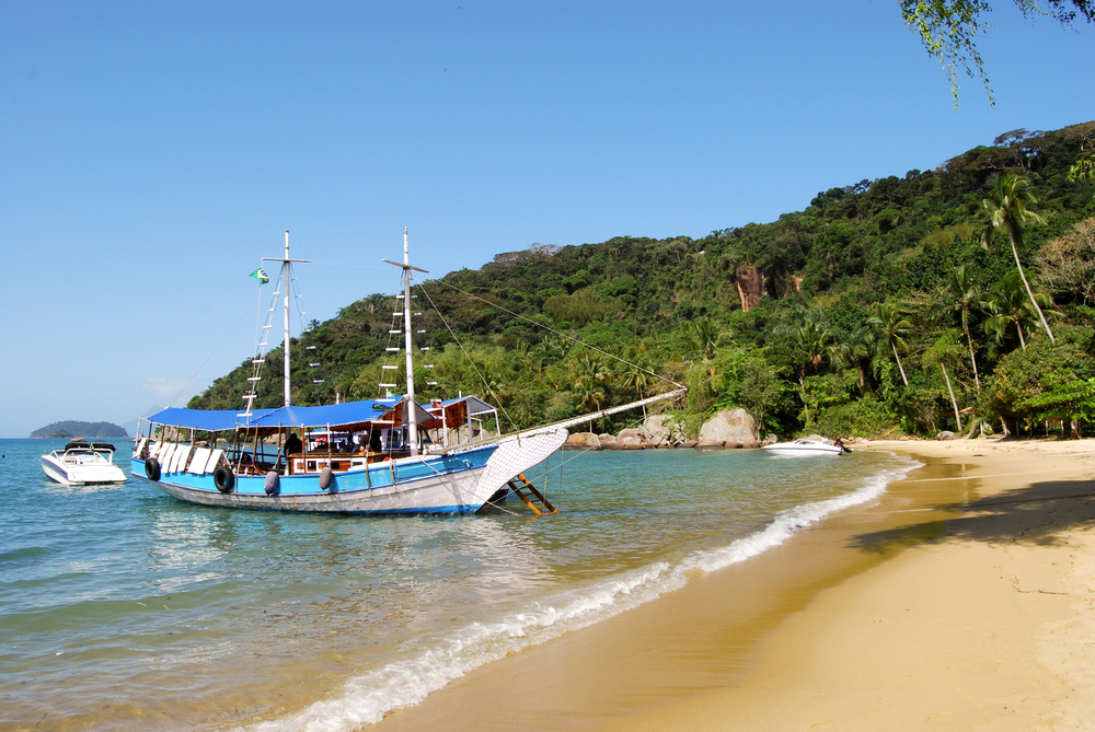 white sand beach with boat and forest background