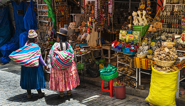 Two local woman wearing traditional clothing in front of a store in a street of the city of La Paz, in Bolivia