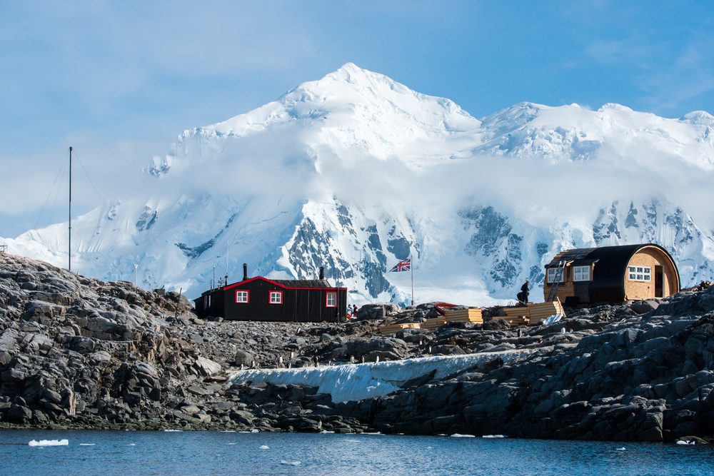 research station port lockroy in antarctica with snow capped mountains in the background