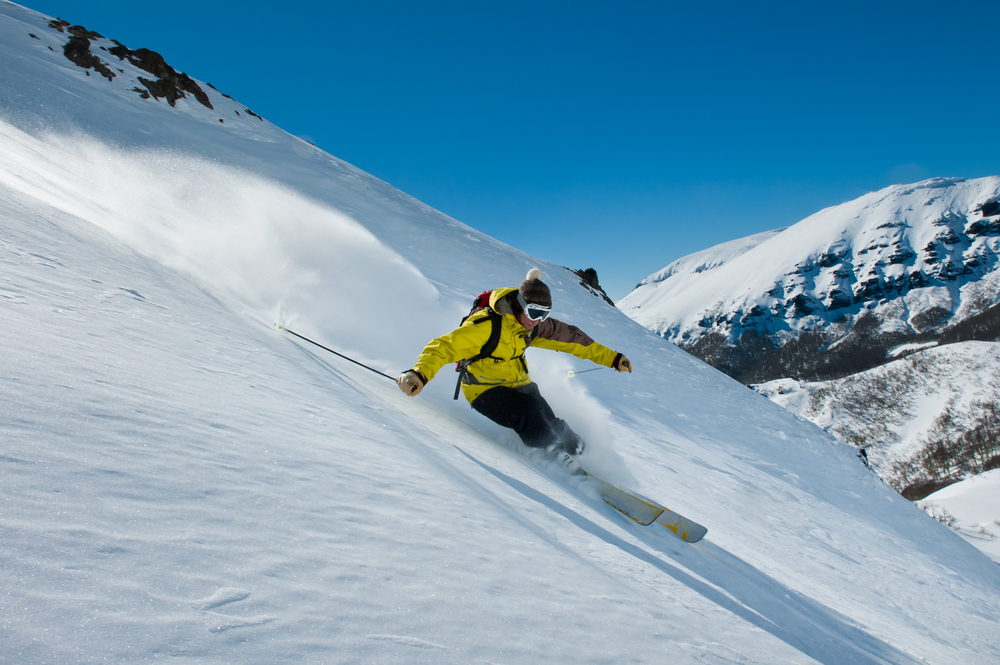 a guy skiing in the fresh snow in the mountains