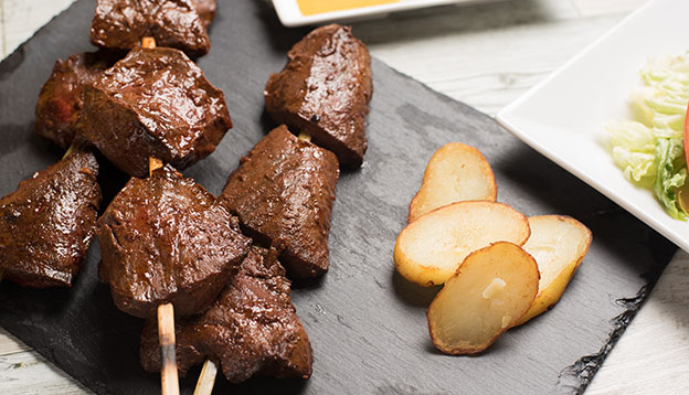Anticuchos - grilled skewered beef heart meat with boiled potato and white corn