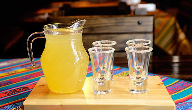 A jug of Canelazo with 4 glasses on a table