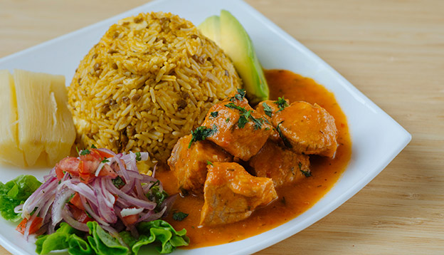 Stew of meat served with rice, lentils, salad and avocado