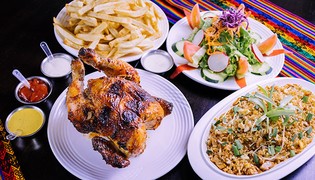 pollo a la brasa - Peru roasted chicken served with salads and chips on a table