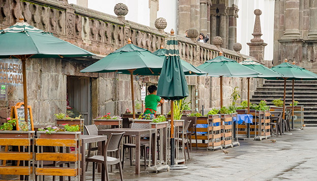 a restaurant with green huge umbrellas and chairs located in the historical centre of old town Quito