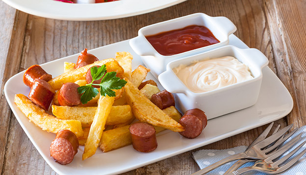 Close up of a plate of Salchipapas. Sauasages and chips