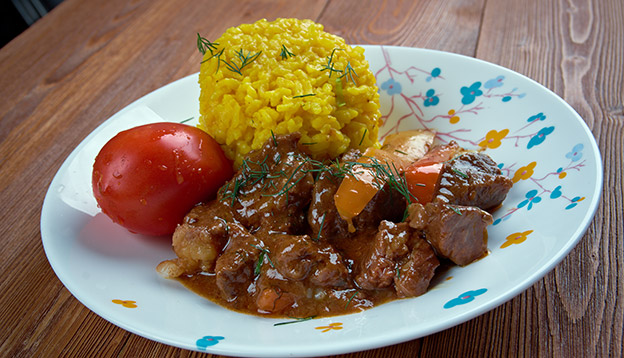 A plate of Seco, an Ecuadorian meta stew served with yellow rice and a tomato