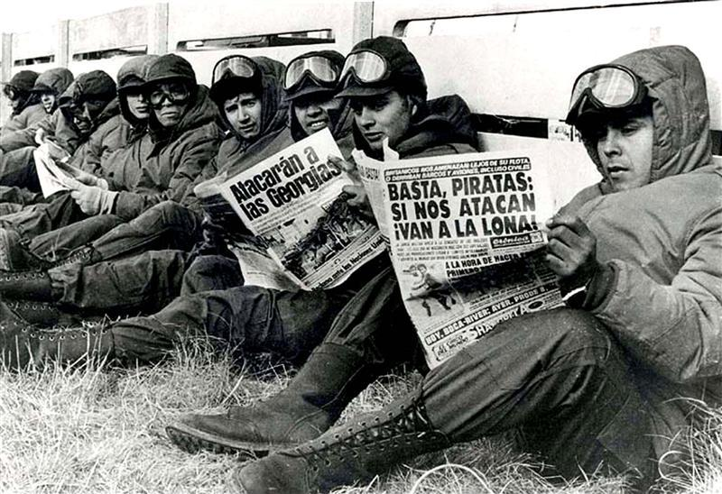 Black and white photo of Argentine soldiers reading the newspaper during the Falklands War.