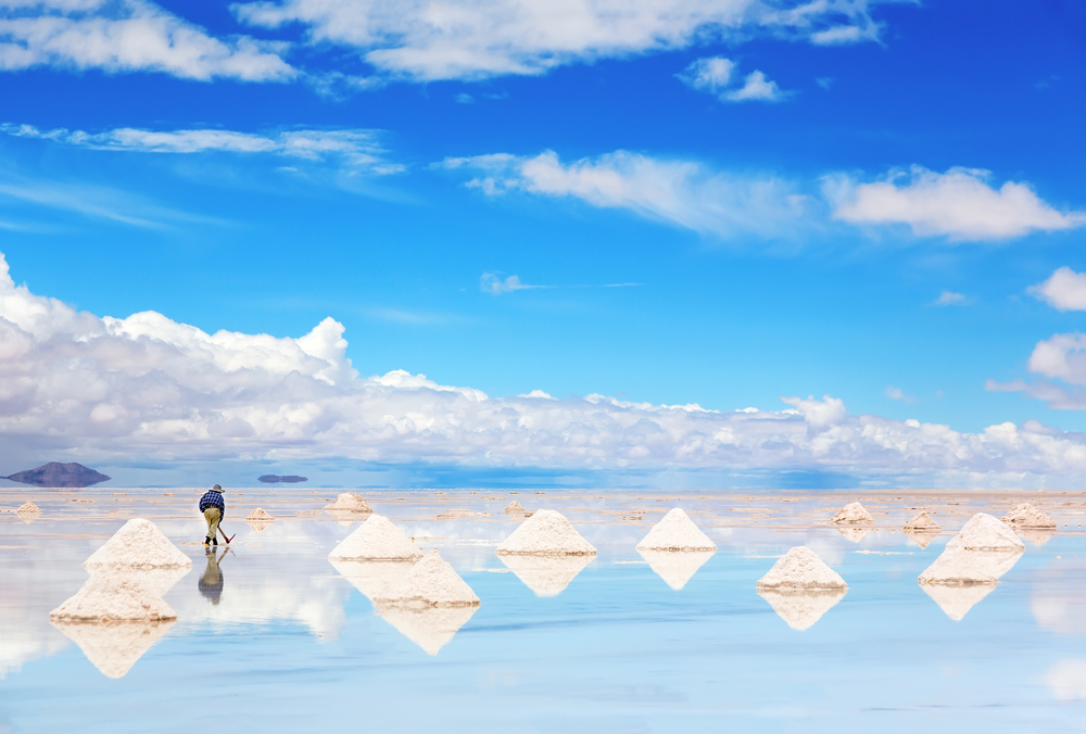 Worker performing harvesting salt on the salt lake Salar de Uyuni.