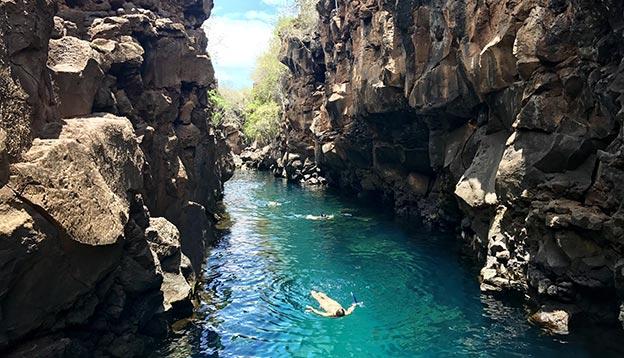 People swimming in a natural pool in Santa Cruz Island, Galapagos