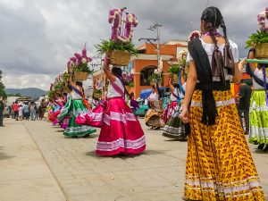OCOTLAN DE MORELOS, OAXACA, MEX.-July 24, 2017. Guelaguetza. Women dance in the streets carrying offerings on their heads and wearing traditional regional clothing. credit shutterstock