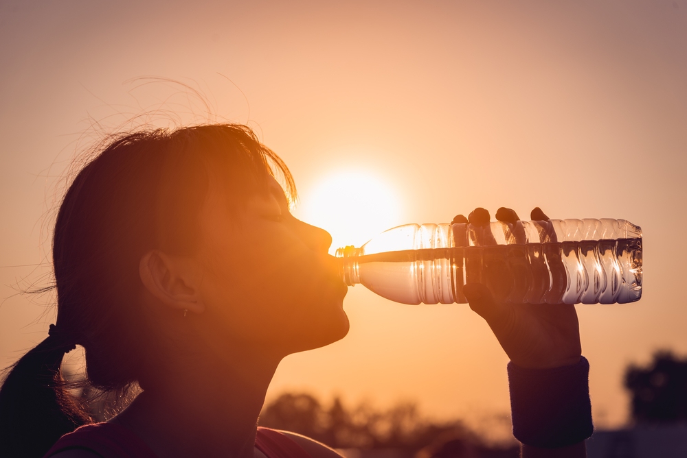 Person drinking bottled water.