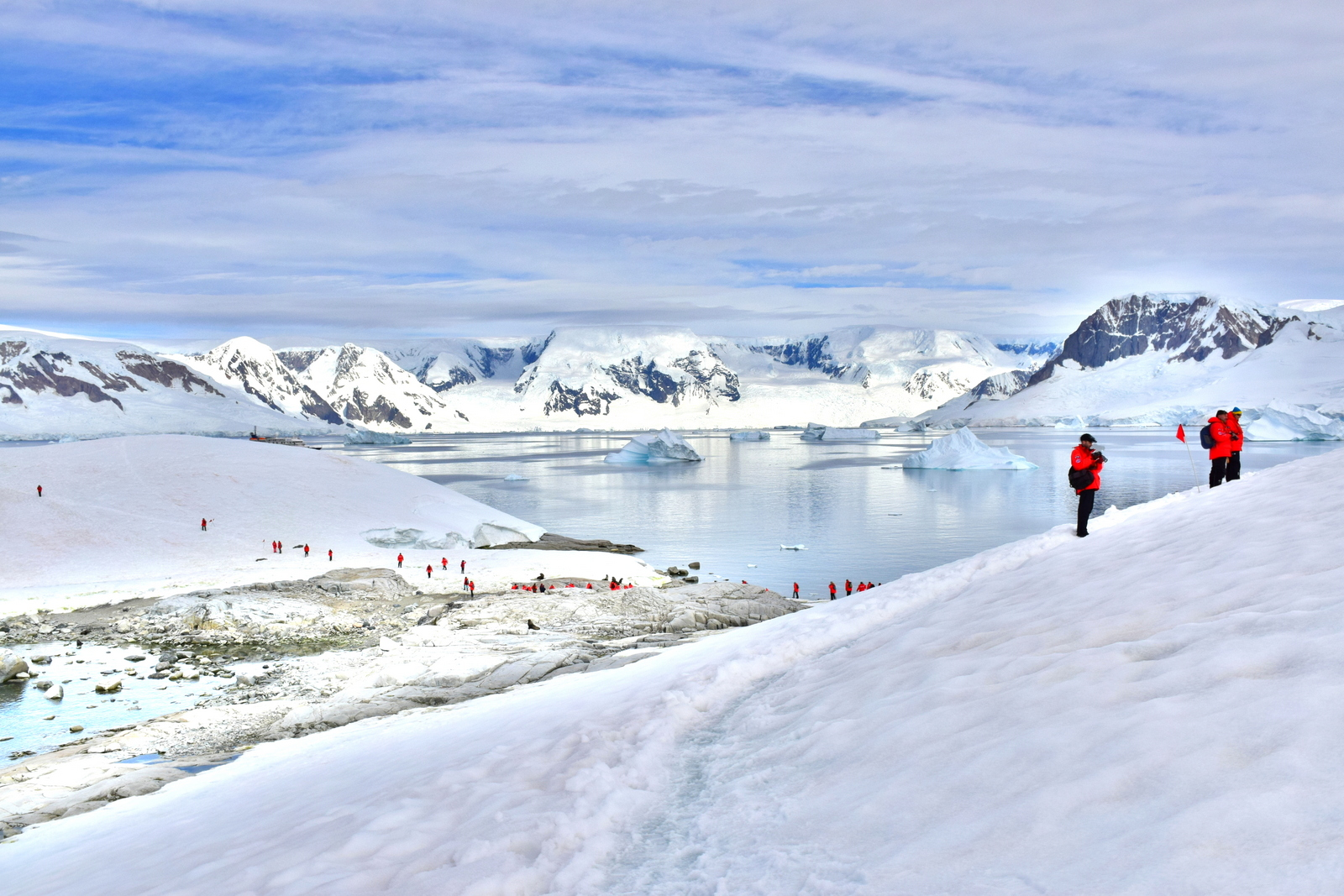 Travelers exploring in Hydruga Rocks in Antarctica with white snow in the background
