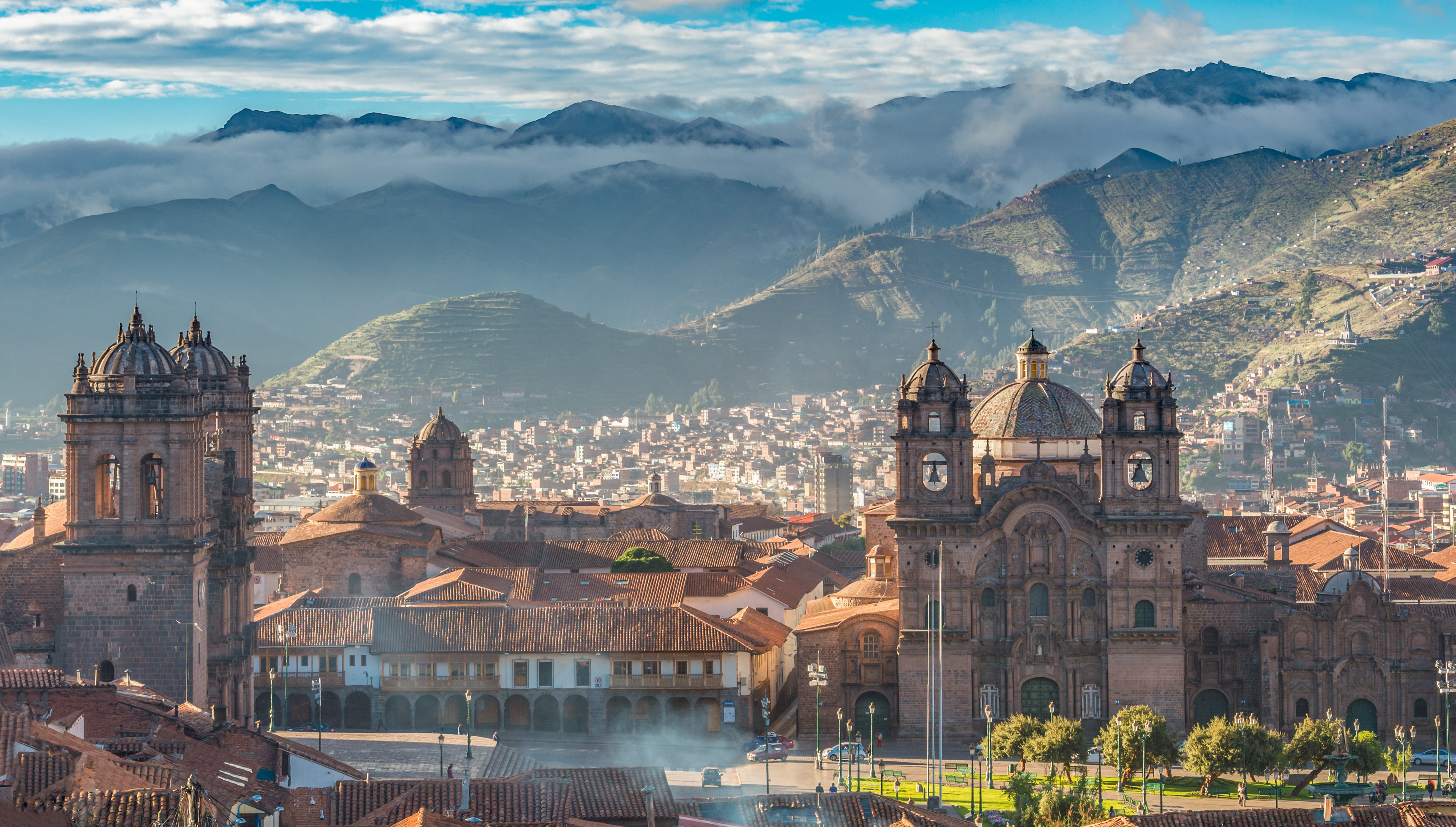 Morning sun rising at Plaza de armas with Adean Moutain and group of cloud, Cusco, Peru