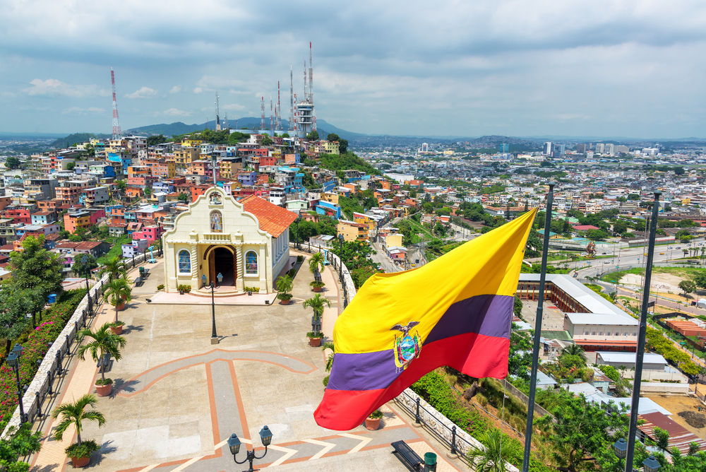Ecuadorian flag on top of Santa Ana hill with a church and the city of Guayaquil in the background in Ecuador