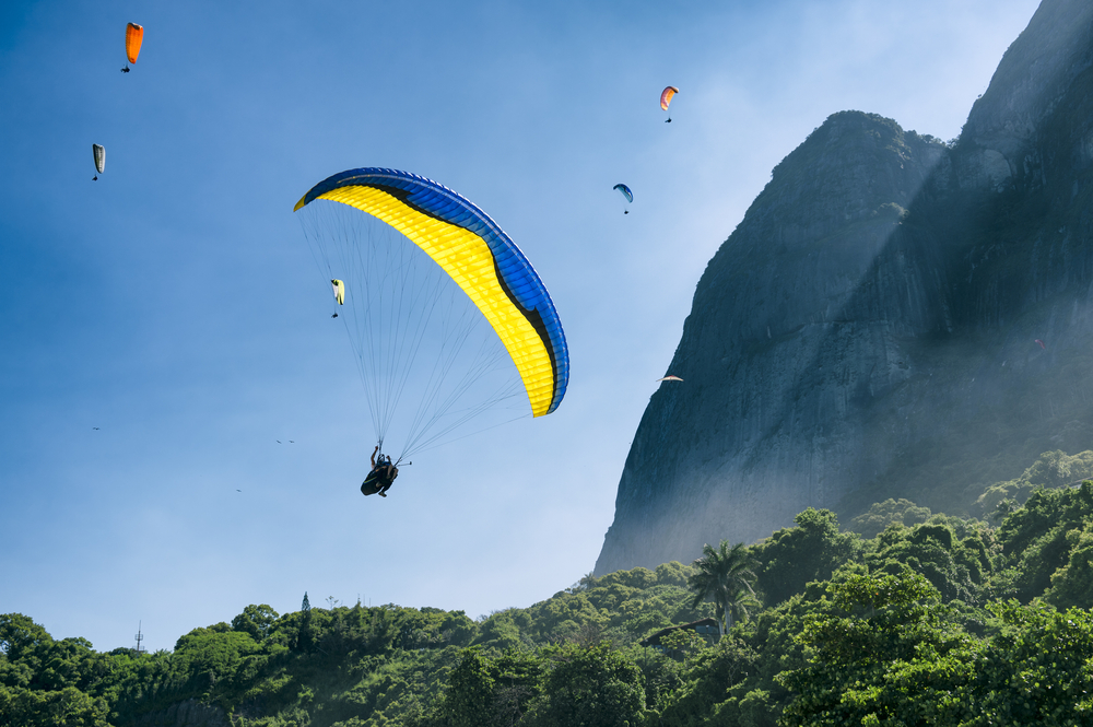 Paraglider passes Pedra da Gavea in Rio de Janeiro, Brazil