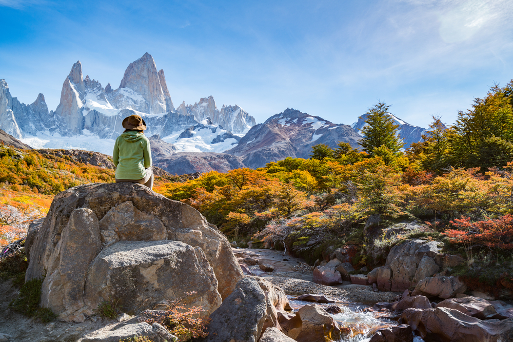 Woman sitting on a rock with trees and mountain view at Fitz Roy, Patagonia, El Chalten in Argentina