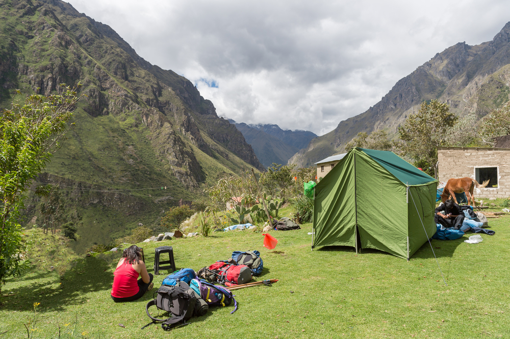 Woman by a campsite with the view of the Andes on the Inca Trail to Machu Pichu from Cusco in Peru