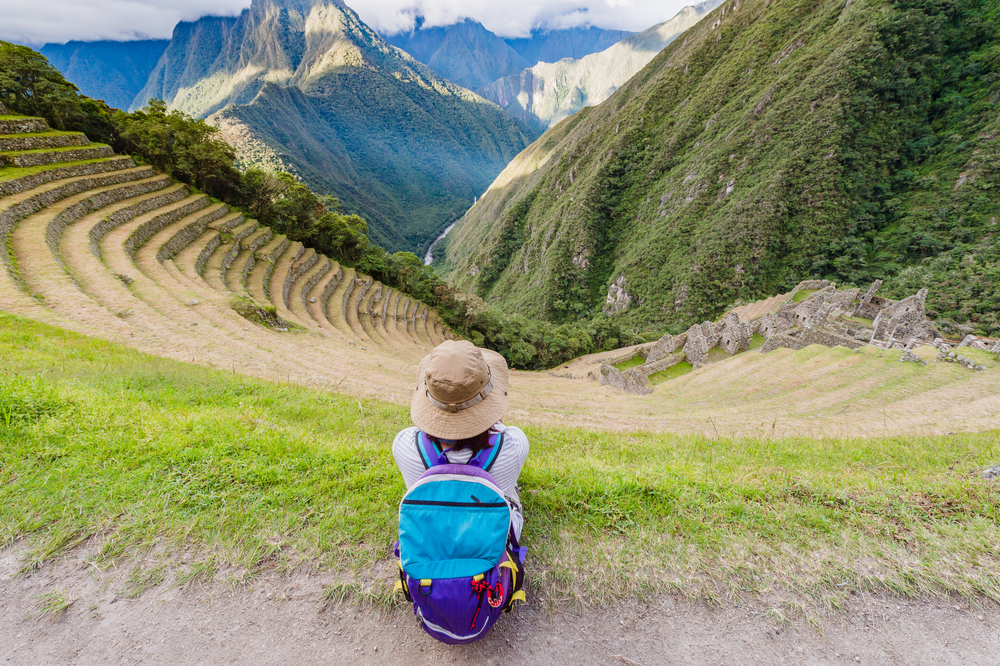 Woman sitting at the Terraced mountainside and buildings at Winay Wayna, The Inca Trail, Machu PIcchu, Cusco, Peru