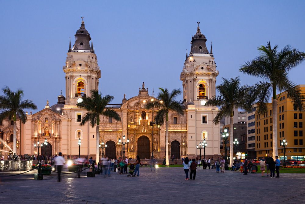 the Basilica Cathedral of Lima at sunset in the Plaza Mayor in Lima, Peru with people walking