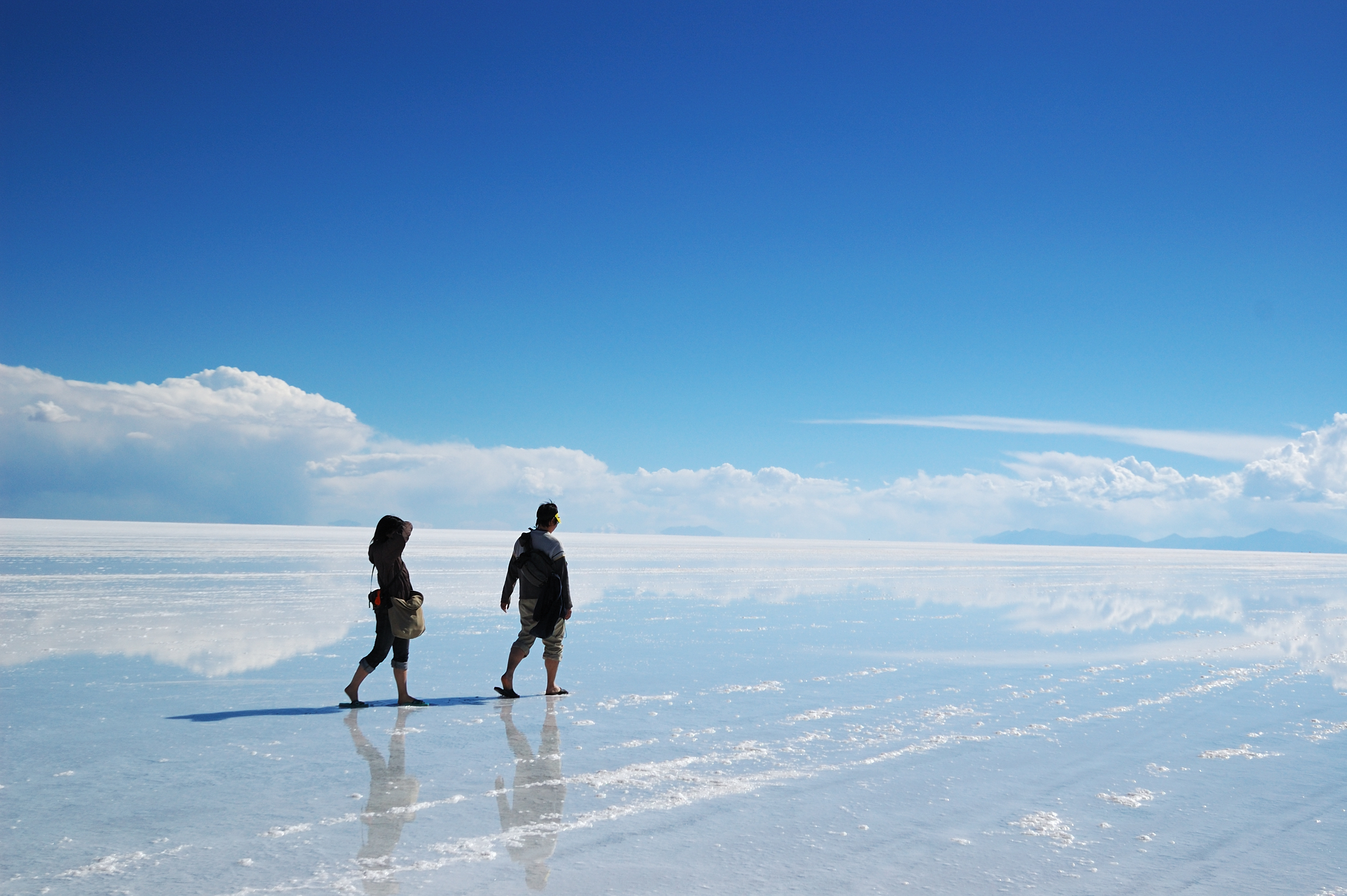 Two people walking on the salt flats in Bolivia in South America