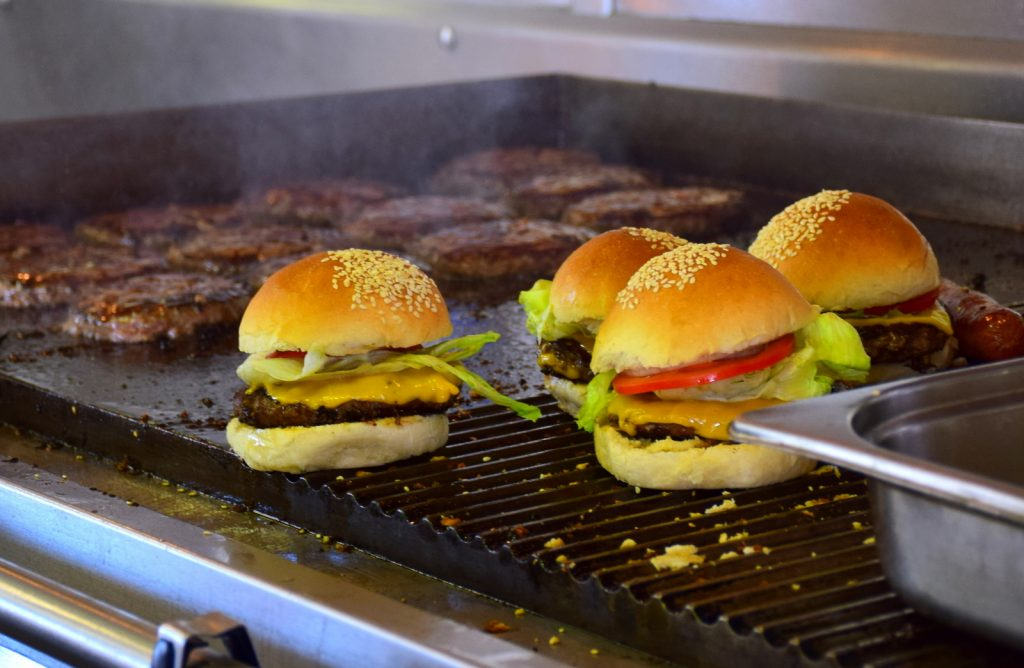 Burger and steaks on a grill.