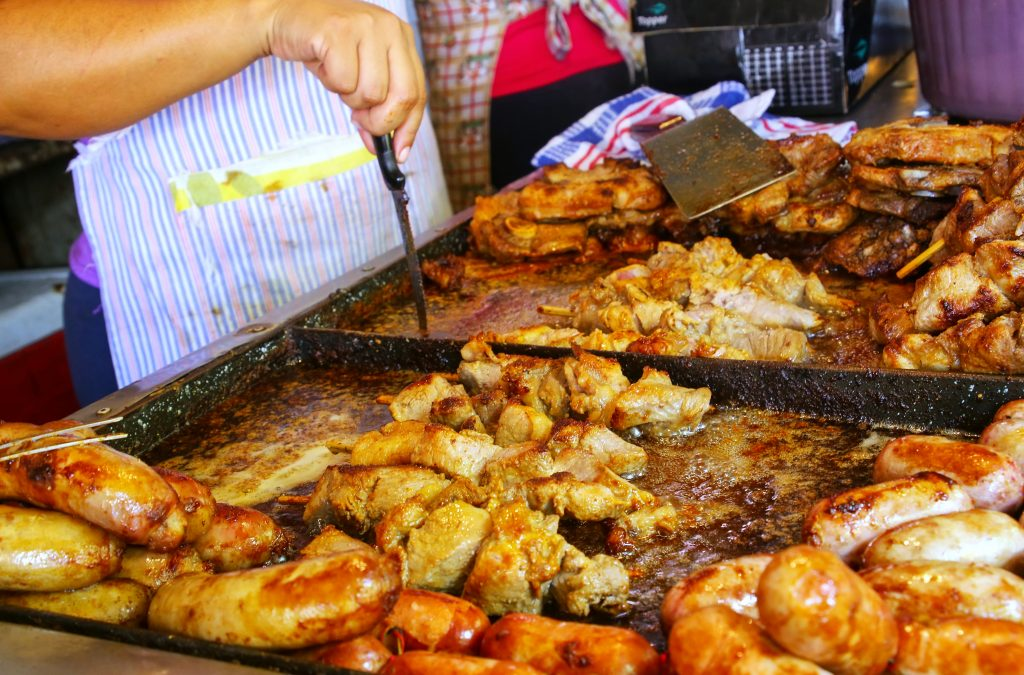Meat is being cooked for asado at Mercado Cuatro in Asuncion, Paraguay. Asado is a traditional dish in Paraguay and usually consists of beef alongside various other meats, which are cooked on a grill
