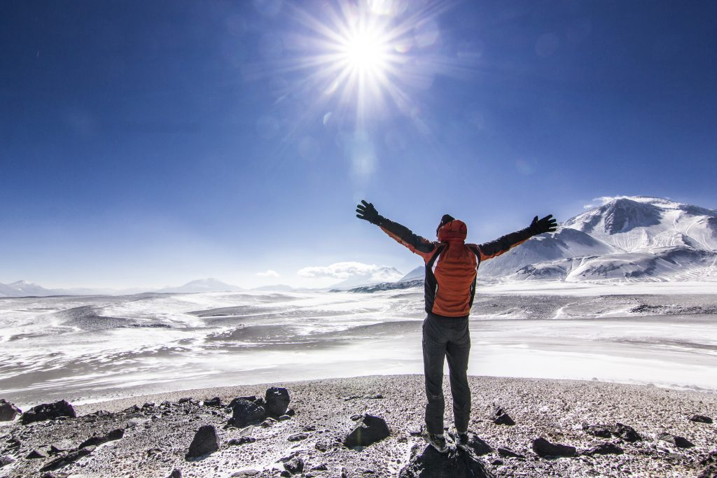 man standing with hands up near ojos del salado volcano in chile