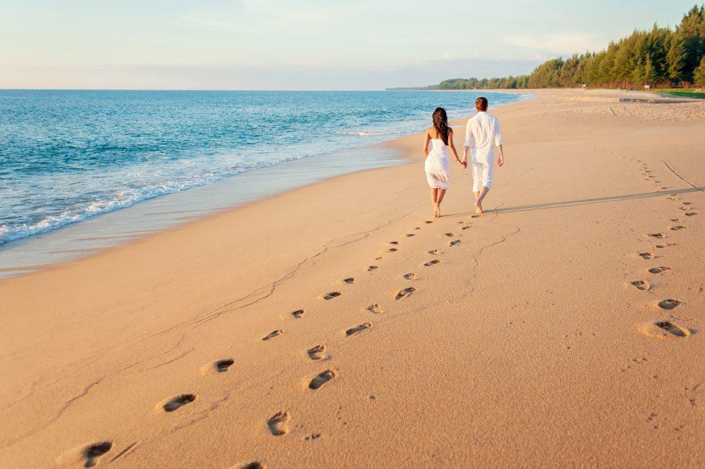 Honeymoon at the sea. Back view of loving couple walking away