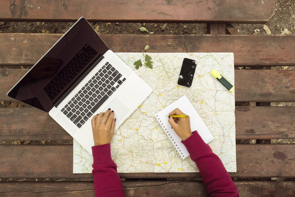 Planning travel on wood table outside with map, laptop, knife, notebook and pen Credit: Shutterstock