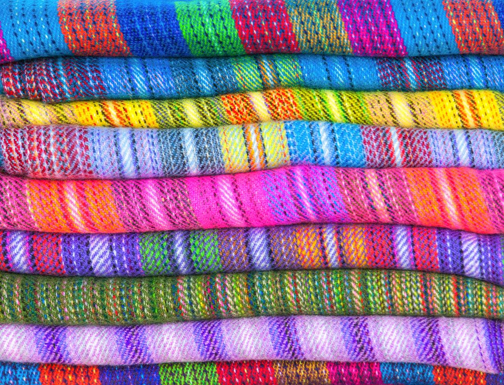 A pile of brightly coloured fabrics of wool lama and alpaca in market Uyuni, Peru, Latin America Credit: Shutter stock