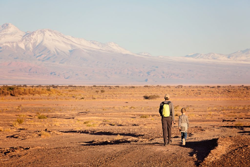 back view of father and son hiking together in atacama desert, chile, driest place on earth, with gorgeous mountain views, active family vacation concept credit shutterstock
