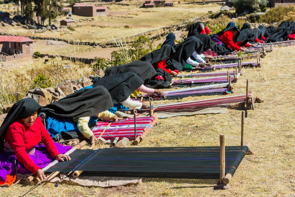 PUNO, PERU - JULY 25, 2013: women weaving in the peruvian Andes at Taquile Island credit shutterstock