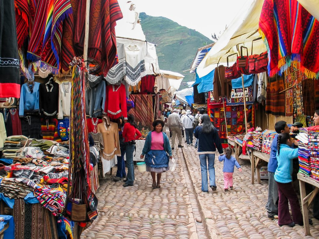 PISAC, PERU - MARCH 2, 2006: Unidentified people on the street of Pisac. It is a Peruvian village in the Sacred Valley. The village is well known for its market every Sunday, Tuesday, and Thursday. credit shutterstock