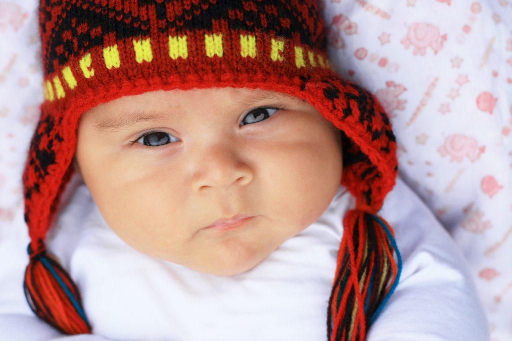 Serious latin baby boy in warm hat - peruvian credit shutterstock