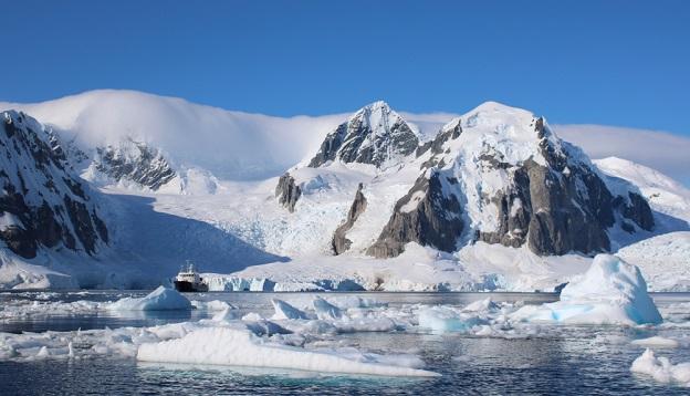 Small passenger vessel between icebergs, Antarctica.