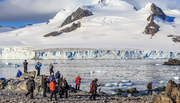 Group of tourists looking at the glacier, Antarctica.