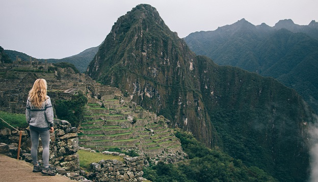 Tourist enjoying the amazing scenery of Machu Picchu. Photo Credit: Shutterstock