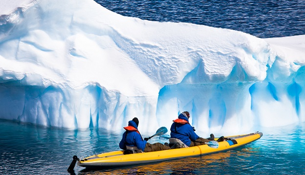 Two men in a canoe among icebergs in Antarctica. Photo Credit: Shutterstock