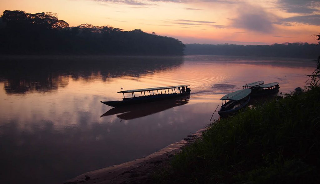 A boat navigating the Tambopata jungle river during a purple and pink sunrise with reflection in the water in the Amazon rainforest in eastern Peru