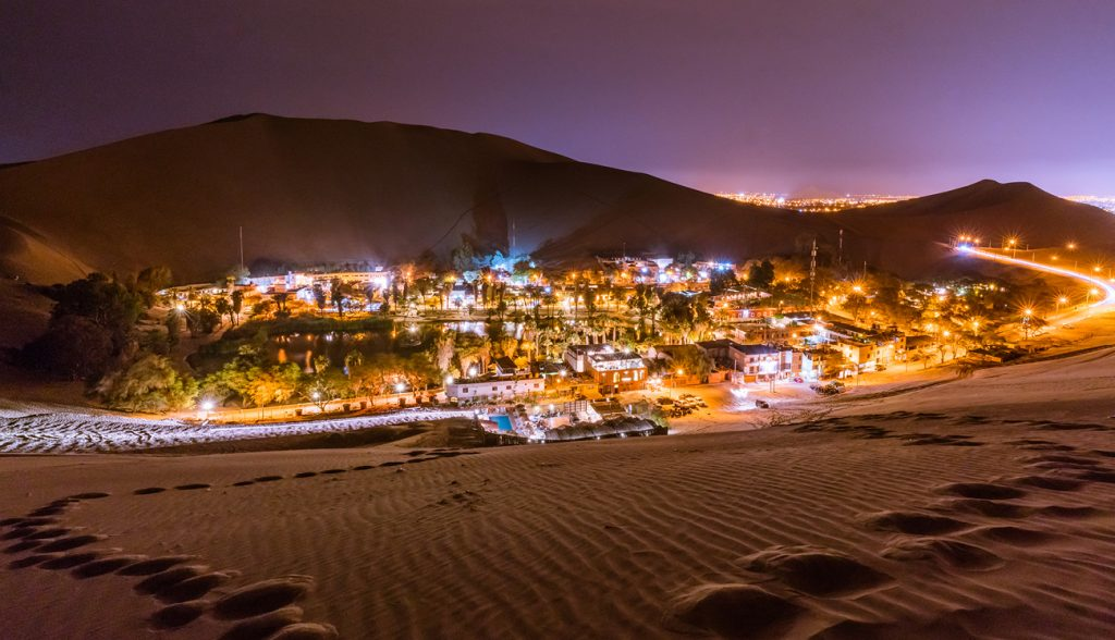 Climbing up the sand dunes here in Huacachina/Peru in order to take a nice landscape picture of this Oasis -